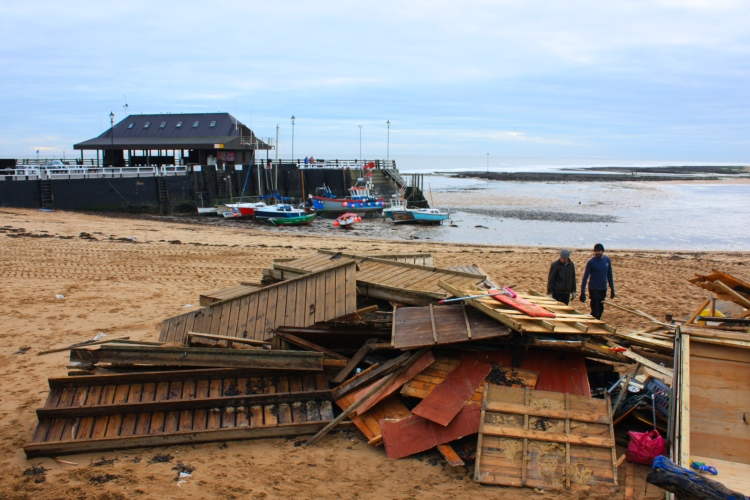 Beach hut owners observe the debris, Viking Bay, December 2013