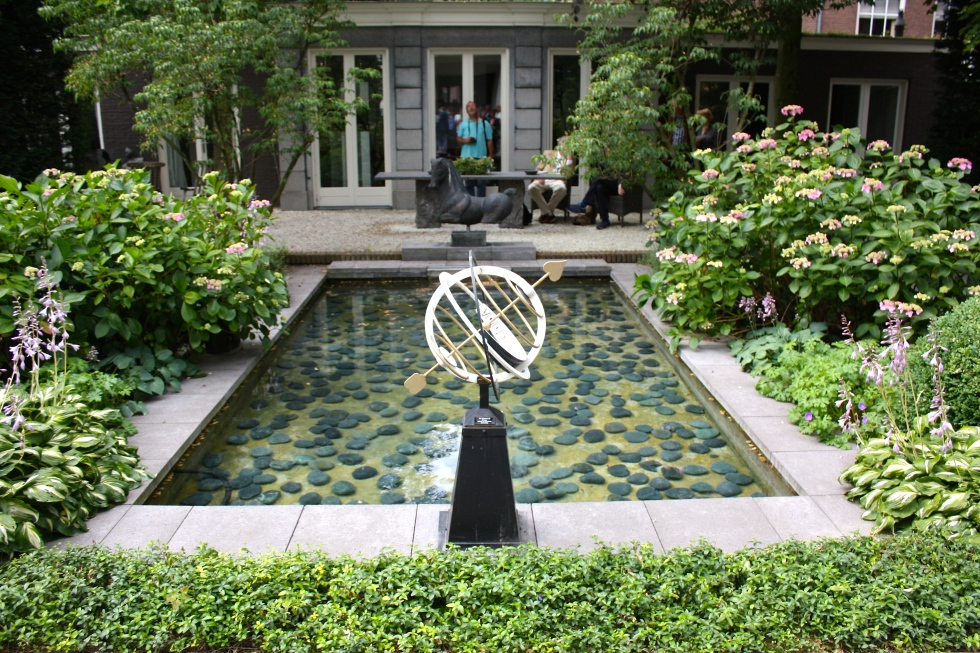 A sober composition of water, paving and symmetrical planting at Amstel 216