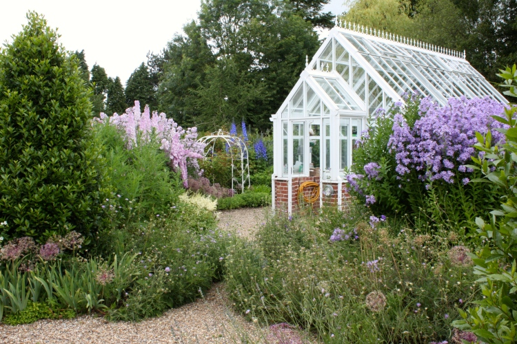 The greenhouse, rising from its own gravel peninsula, lies on one edge of the Pastels Garden