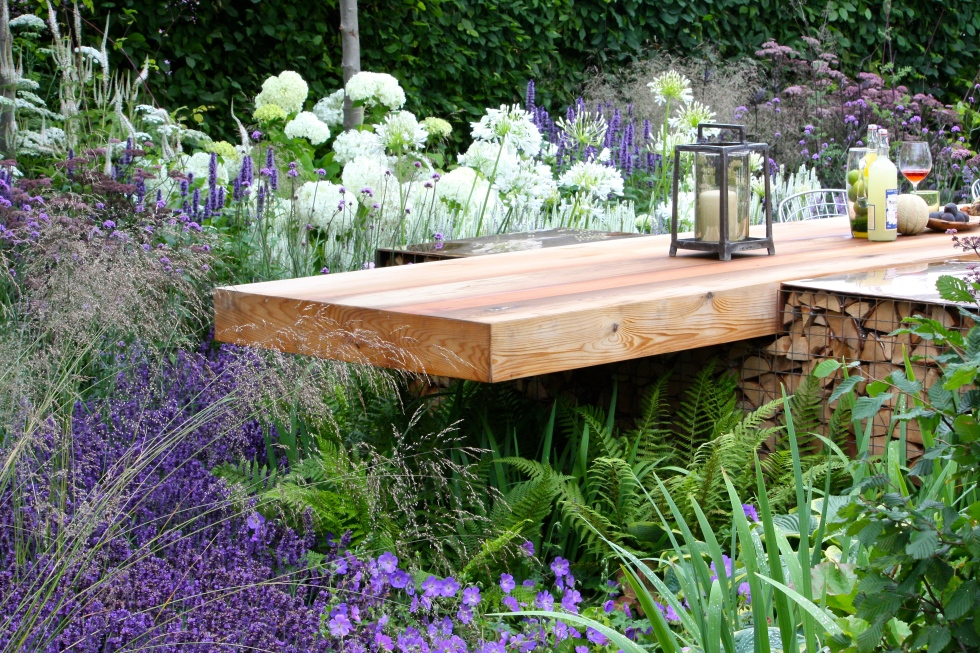 The dining table cantilevers over an area of lush planting