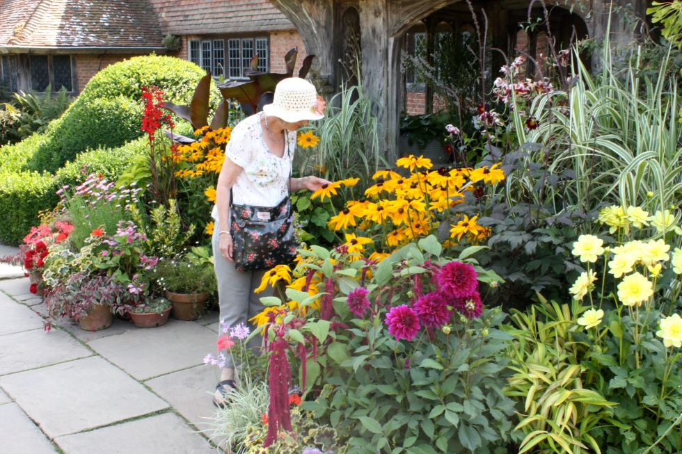 A visitor admires the dazzling display of potted plants outside the front entrance to Great Dixter