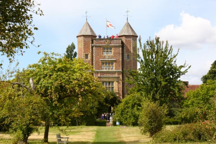 Sissinghurst's splendid tower rises from the sward of the freshly scythed orchard