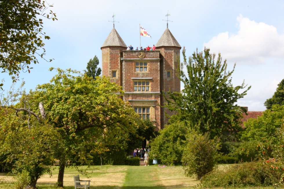 Sissinghurst's splendid tower rises from the sward of the freshly scythed orchard