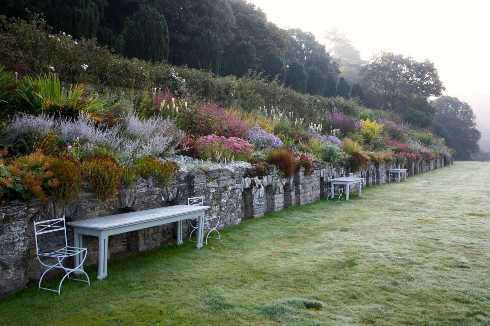 The early morning mist hovers above the herbaceous border, amongst the longest in England