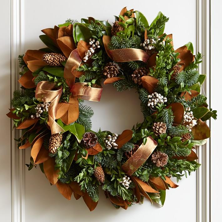 This stunning wreath combines Magnolia grandiflora leaves, box, noble fir, tallow berries (Triadica sebifera) and natural pinecones