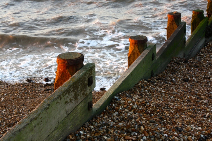 The last of the winter sun warms the rusty posts supporting Whitstable's groynes