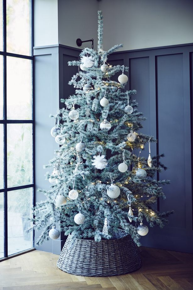 A silver-grey tree dressed lightly with white ornaments and dewdrop lights is simple yet festive