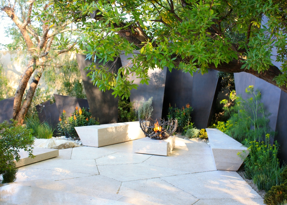 A quiet seating area at the end of the garden centred around a hammered bronze fire bowl created by James Price
